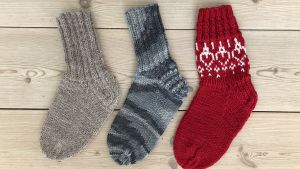 Kolme erilaisia sukkia lattialla