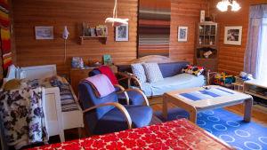 Vardagsrummet i en sommarstuga med stockväggar, utdragbara bäddsoffor, en blå fåtölj och ett matbord med en blommig bordduk.