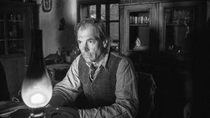 En man sitter i dunklet vid en fotogenlampa.