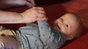 Soiva syli: äiti leikittää vauvaa