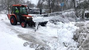 Liten traktor plogar snö på gångbanan.