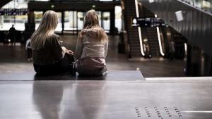 Två flickor med långt hår sitter med ryggen mot kameran på en bänk på köpcentret Tripla i Helsingfors.