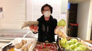 En kvinna med munskydd står bakom ett bord med matvaror på Hon håller tomater, potatis, kål och bröd i händerna.