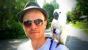 Filmregissören Dome Karukoski, en av vegas sommarpratare 2014 har en vit papegoja på axeln. I solglasögonen speglas fotografen och en vän. Det är sommar