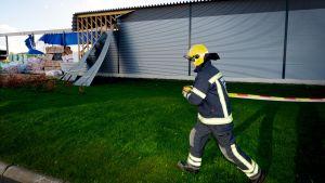 Brandman jobbar med att röja upp efter stormen Valio.