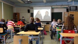 Oppilaat katsovat luokassa videota
