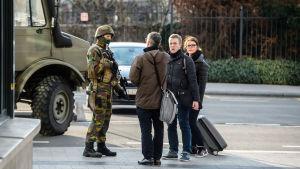 Fotgängare pratar med en soldat i Bryssel efter terrorattackerna den 22 mars 2016.