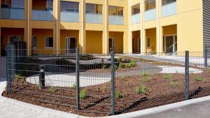 En nyplanterad liten trädgård bakom stängsel vid ett servicehus.