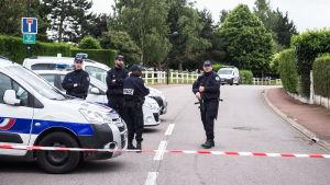 Poliser står vakt nära de mördade polisernas hem i Parisförorten Magnanville den 14 juni 2016.