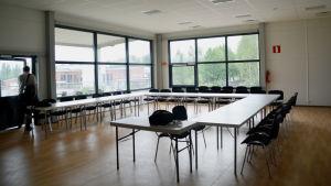 Ett rum med två stora fönster. I rummet står flera bord med stolar brevid.