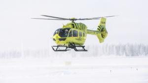 En räddningshelikopter i färd att landa på en snöig landningsplats.