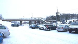 Bilar är parkerade nedanför järnvägsbron i Karis.