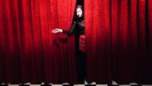 Elina Iida Sofia Hirvonen kuvauksissa punaisen verhon takana.