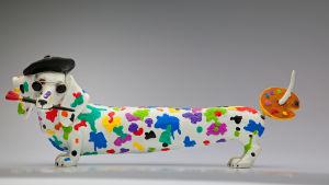 En överdrivet lång hund med färggranna fläckar samt en pensel i munnen och en palett på svansen.