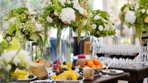 En dukat bord med stora blomsterarrangemang, plockmat och vinglas med rödvin.