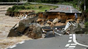 En man försöker korsa en kollapsad väg i Higashihiroshima i Japan.