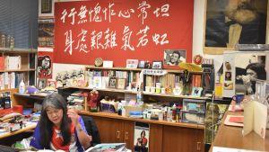 Den förra parlamentsledamoten Leung Kwok-hung, en äldre man med långt gråsvart hår klädd i t-skjorta med norkoreas flagga, sitter i ett arbetsrum med ett rött plakat i bakgrunden och böcker på hög överallt.