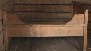Närbild på en gammal träsäng med ena långsidan fäst i väggen.
