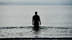 Mörk bild av karaktären Christian som går ut i havet.