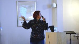 Pernilla Lindroos föreläser, håller i en pärm i en handen och mikrofonen i andra, kollar till sidan mot skärmen.