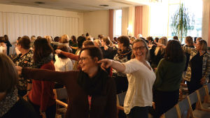 En grupp människor i en föreläsningssal står upp och pekar åt ett håll.
