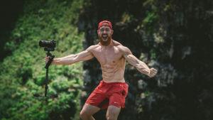 Lihaksikas mies punaisissa shorteissa levittää käsiään ja pitelee kameraa.