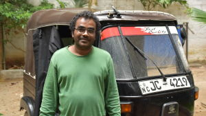 En lankesisk man i grön tröja står framför en svart Tuktuk.