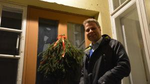 Kim Söderström i blå rock står vid en dörr med granris i rött sidenband.