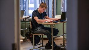En koncentrerad Alex sitter vid pulpeten.