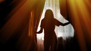 Silhuett av en kvinna som kikar ut genom ett fönster och håller en tung gardin åt sidan.