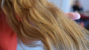 Lockigt, brunt hår i närbild.