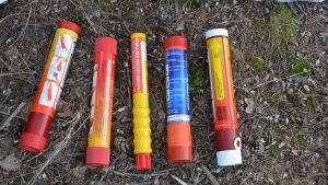 Fem nödraketer i rött, orange och gult ligger på en barrig stig.
