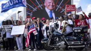 En samling pro-Trump-demonstranter uppställda framför väggpoerträtt av presidenten