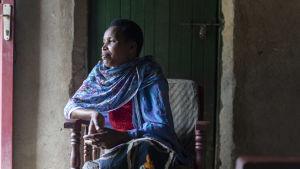 Rwandiern Jacqueline Mukamana sitter och flätar en korg.