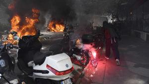 Till höger en demonstrant med bengalisk eld. Till vänster två brinnande fordon.