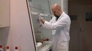 Tony Cederberg undersöker ett vattenprov i ett laboratorium på Husö