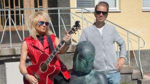 En man med långt blont hår och röd läderväst spelar på en gitarr. Berdvid honom en man som ler. De står vid en fontän.