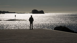 Mies seisoo meren rannalla.