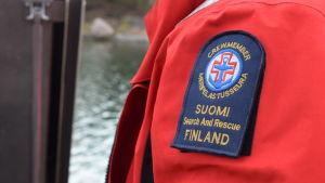 Bild på en arm med en lapp på armen med sjöräddningssällskapets logo och text.