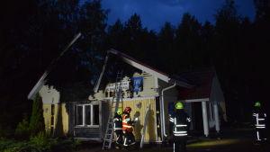 Några brandmän står vid ett förkolnat, ljusgult trähus som förstörts i en brand.