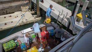 Människor lastar av en båt.