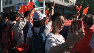 En kvinna med Kinas flagga målad på kinden tar en selfie under Kinas 70 års jubileum.