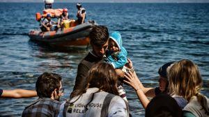 Migranter som anländer 16.9.2019 till Lesbos från Turkiet. I bildens mitt ses en man med ett spädbarn, i bakgrunden en ribbåt.