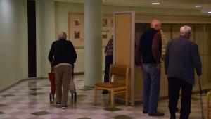 Äldre personer går i en korridor på dagverksamheten i Ekenäs.
