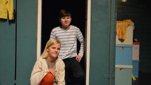 Två barn sitter på huk på en teaterscen. I bakgrunden färgglada lådor.