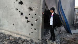En libysk pojke undersökte en byggnad strax öster om Tripoli efter en flygattack under helgen.