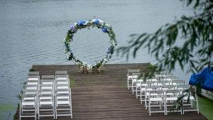 En vigselbåge dekorerad av blommor ute på en brygga.