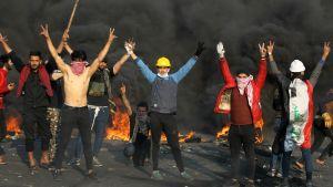 Unga irakiska demonstranter visar segertecknet mitt under sammandrabbningar med kravallpolis i Bagdad på måndagen.