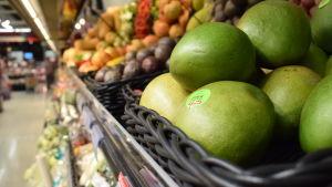 Frukter, med mango längst fram, i en butikshylla i matbutiken.