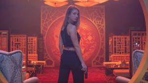 Nainen seisoo asekädessä selin, mutta yläkeho kääntyneenä katsojaan punaisessa huoneessa.